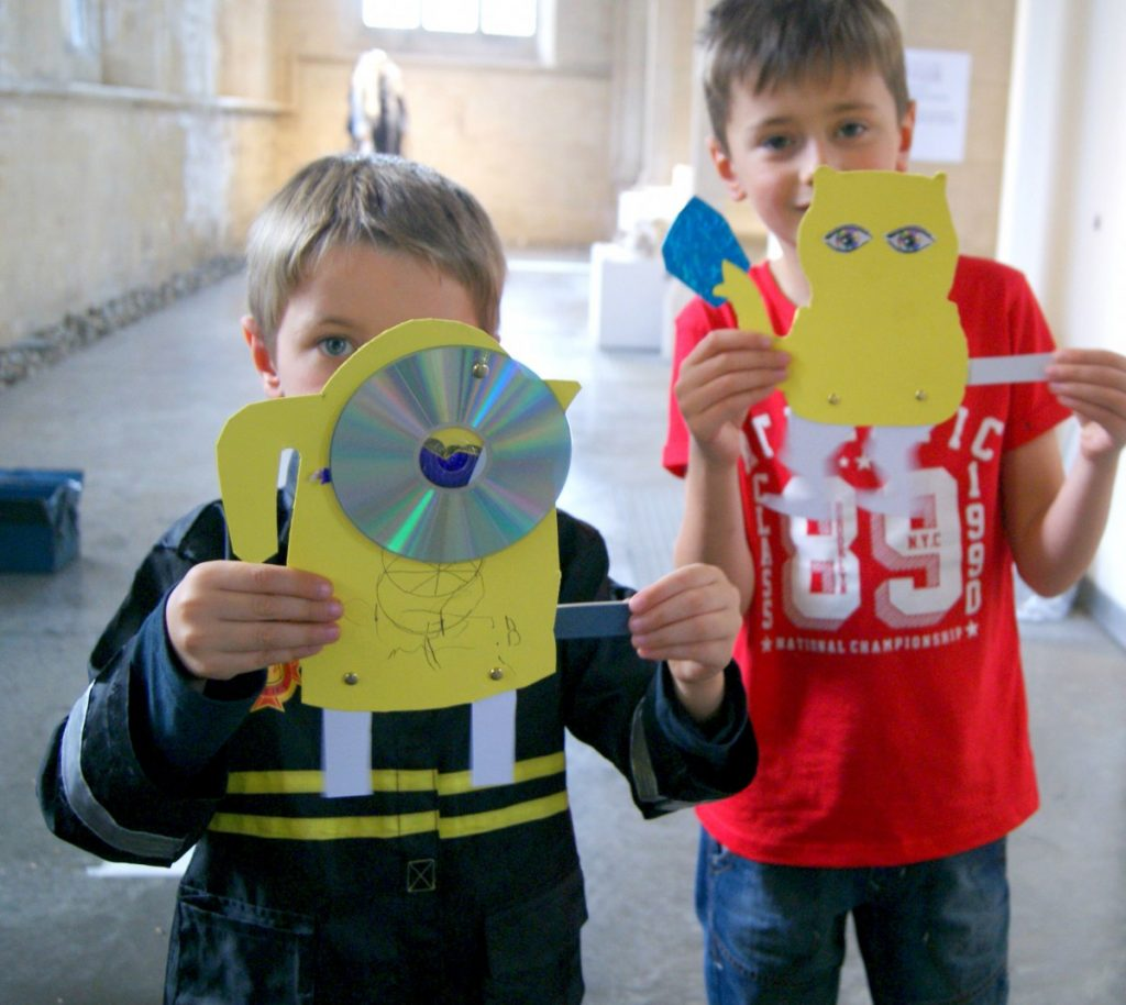 Two boys holding up paper monsters, Activity Table. Artivities, 20-21 Visual Arts Centre