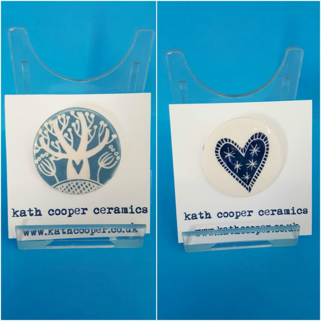 Badges - Blue tree (left) and dark blue heart (right)