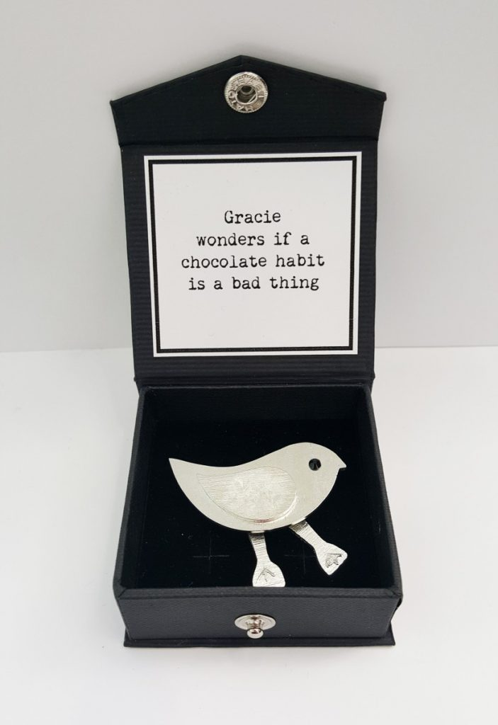 "Gracie Brooch, caption on box reads: ""Gracie wonders if her chocolate habit it a bad thing."""