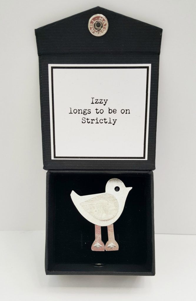 "Izzy Brooch, caption on box reads: ""Izzy longs to be on Strictly."""