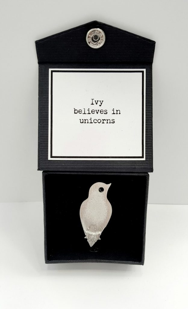 "Ivy Brooch, caption on box reads: ""Ivy believes in unicorns."""
