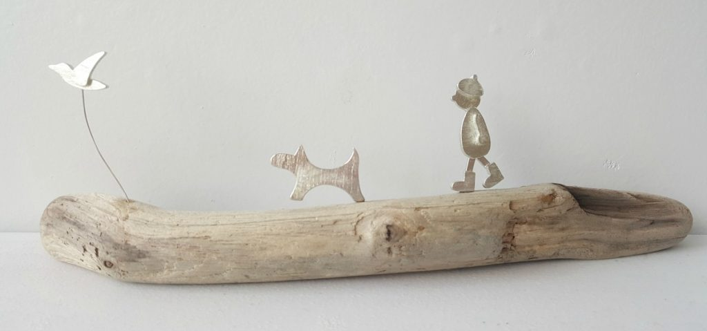 Yvette Brown - Man walking dog with bird flying by, wooden base.