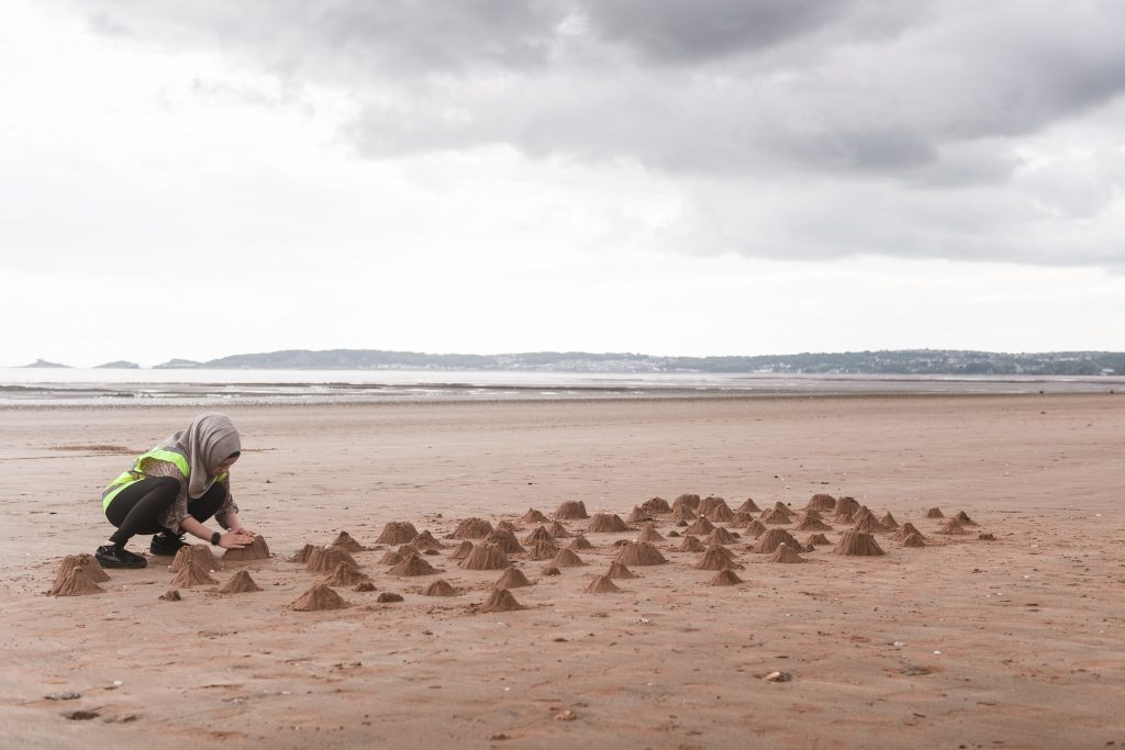 A person on a beach creates a range of small mountains from sand