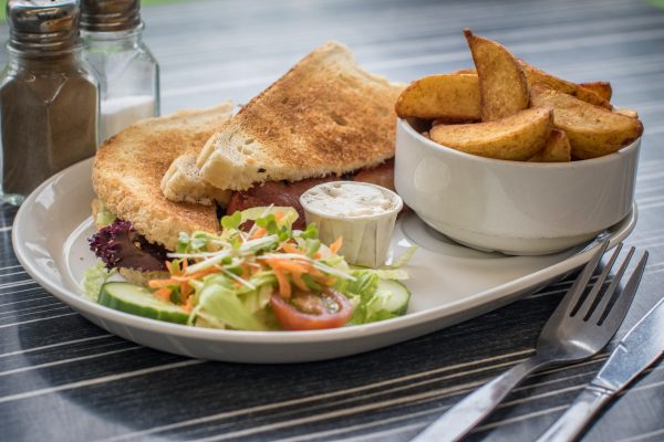 Toasted sandwich served with wedges and salad