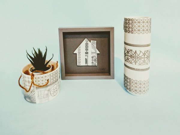 Ceramic hanging planter, framed silhouette of a house and cylindrical vase by Alex Allday