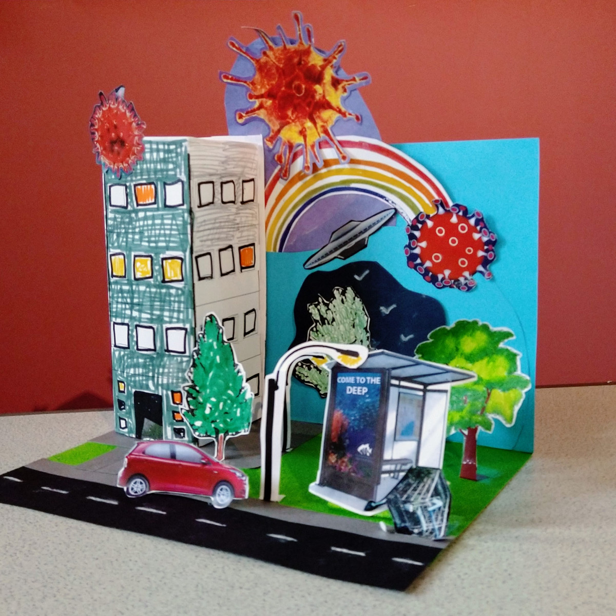"""""""Covid Over the Rainbow"""" - a 3D cardcraft activity which includes a towerblock, bus stop, flying saucer, rainbow and Covid virus cutouts"""