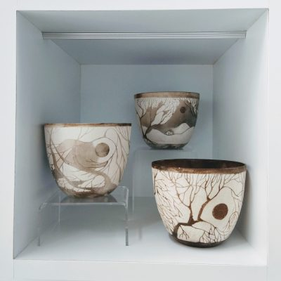 Three smoke fired bowls by Clare Humphry showing silhouetted trees and landscapes