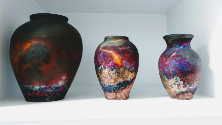 Three Raku vases by Pat Armstrong, with abstract iridescent glazes