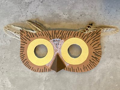 Cardboard owl mask decorated with feather trim