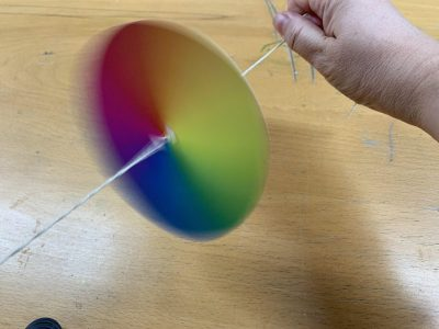Multicoloured spinner - a spinning disc on length of string