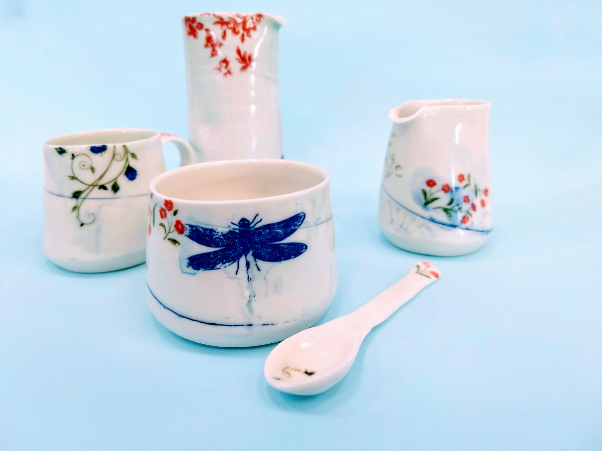 White handmade ceramic jugs, cup, sugar bowl and spoon by Helen Harrison, all with soft designs of natural motifs in red and blue