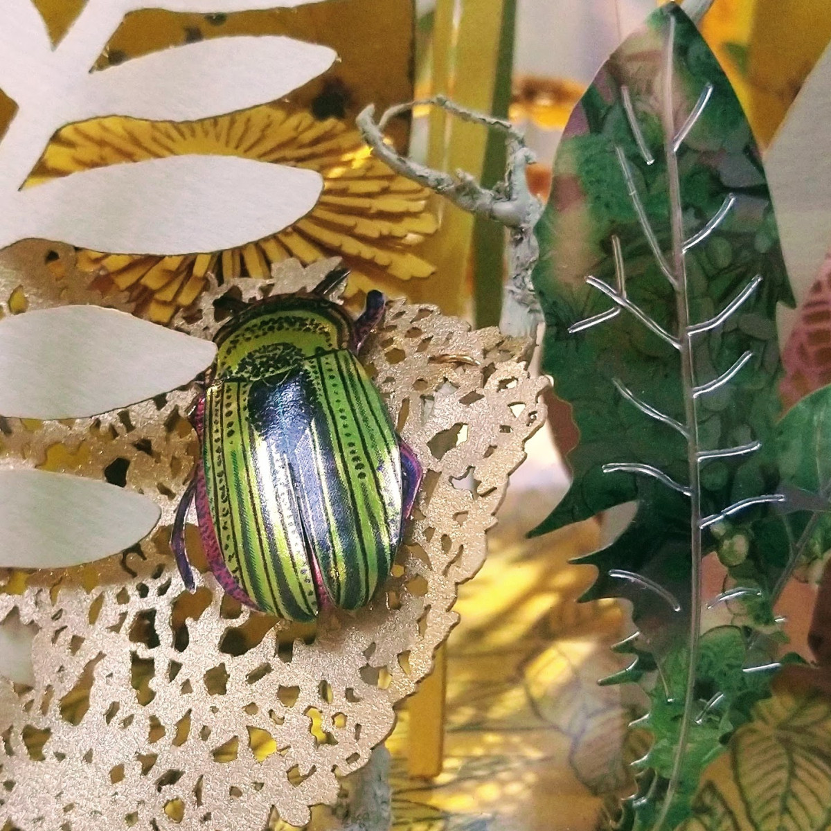 Detail from a Melanie Tomlinson work, showing a bright green metalwork beetle among stylised cutout metal foliage.