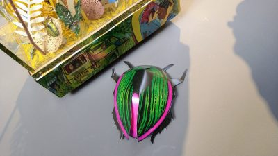 colourful papercraft 3D beetle next to an artwork containing a smaller 3D beetle in coloured metal