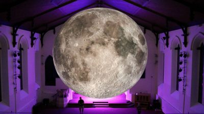 Museum of the Moon by Luke Jerram illuminated with purple light