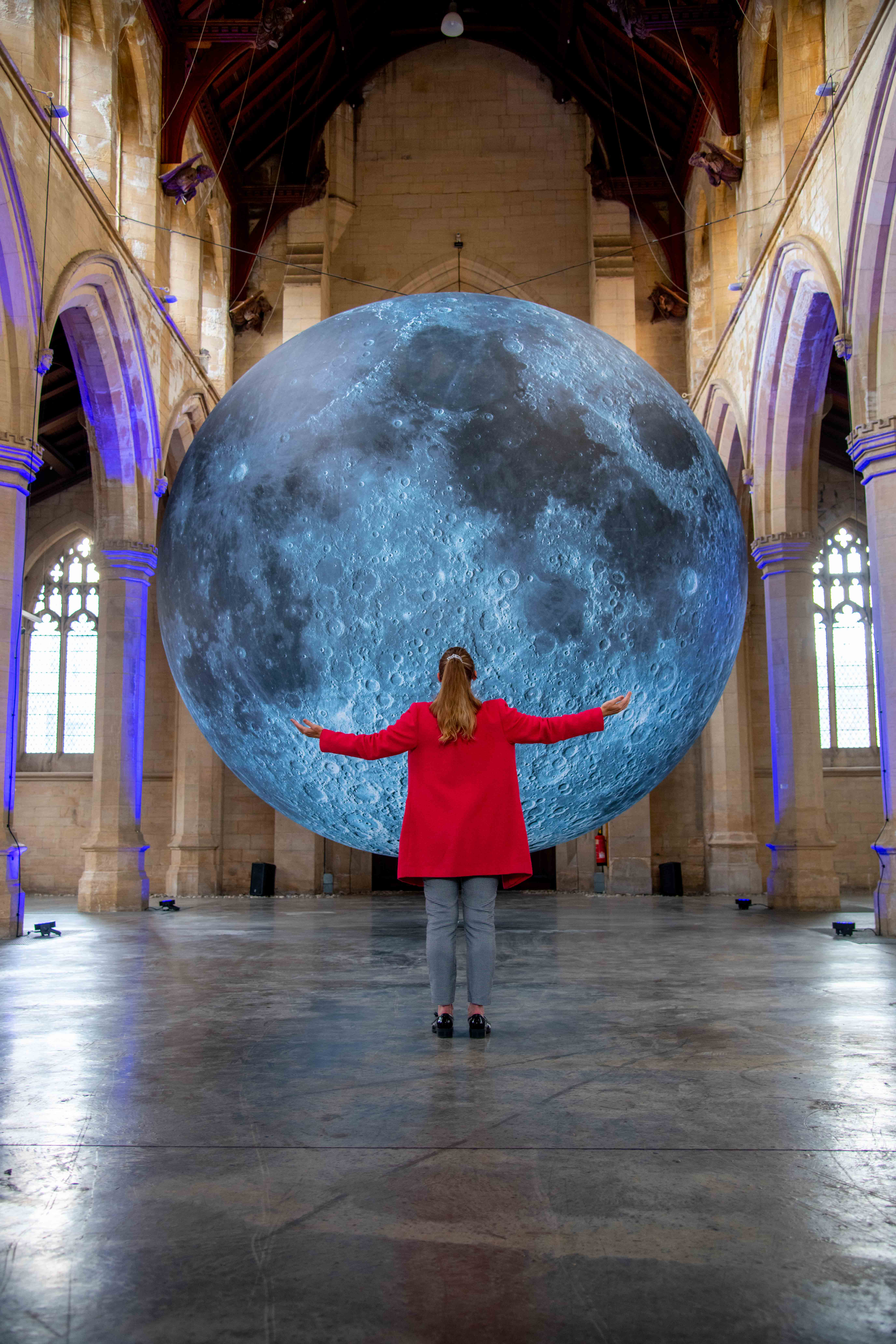 figure in a red coat standing in front of Museum of the Moon