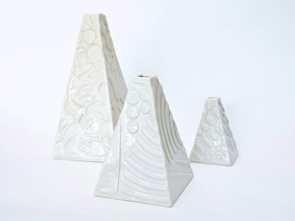 White pyramid shaped ceramic bottles with a relief design, by Karen Hanvidge