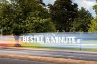 Photo of large letters spelling out the words 'Be still a minute' at the side of a busy road