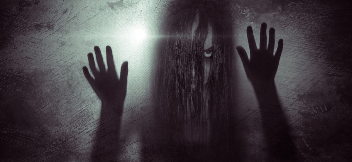 Spooky monochrome image of a woman with hair draped over her face staring at the viewer