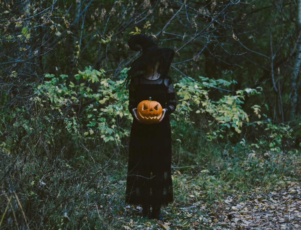 Spooky muted photograph of someone dressed as a witch holding a carved pumpkin and standing in a wood