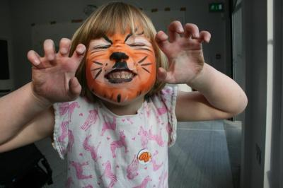 Girl with tiger face paint growling
