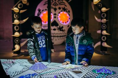 Two boys interacting with the projected animations of Synchronicity in the Animotion exhibition