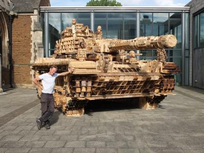 Peter Mountain standing next to his life size wooden sculpture of a tank
