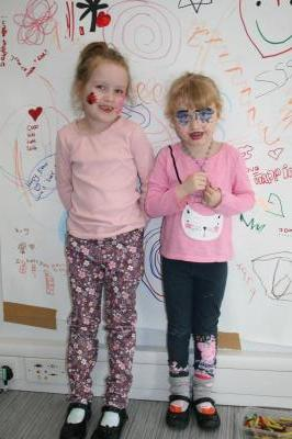 Two girls with face paint standing in front of a whiteboard